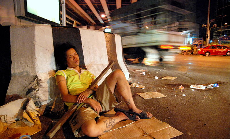 Woman asleep with a large stick in her arms beneath the Thai-Belgian bridge at Rama 4/Sathorn/Wireless road intersection