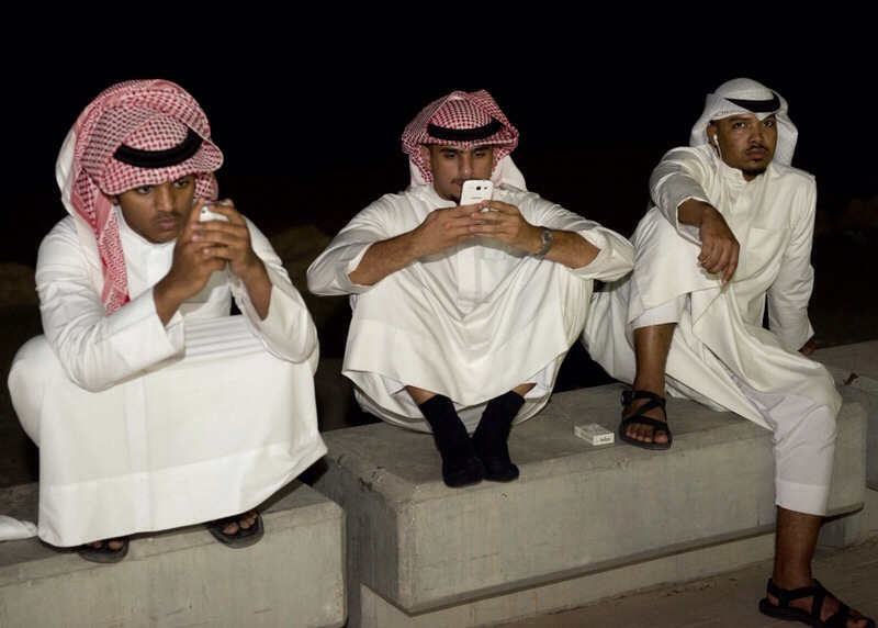 Kuwaiti men look at their cell phones