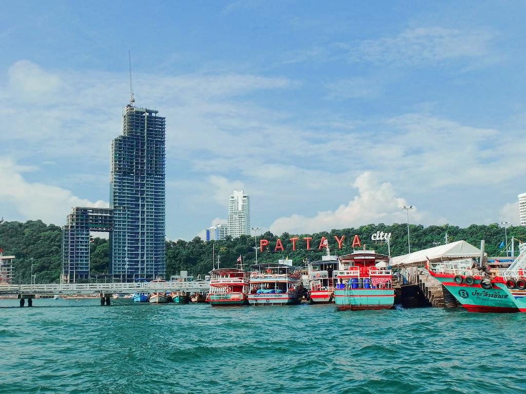 Pattaya City sign and boats at Pattaya pier