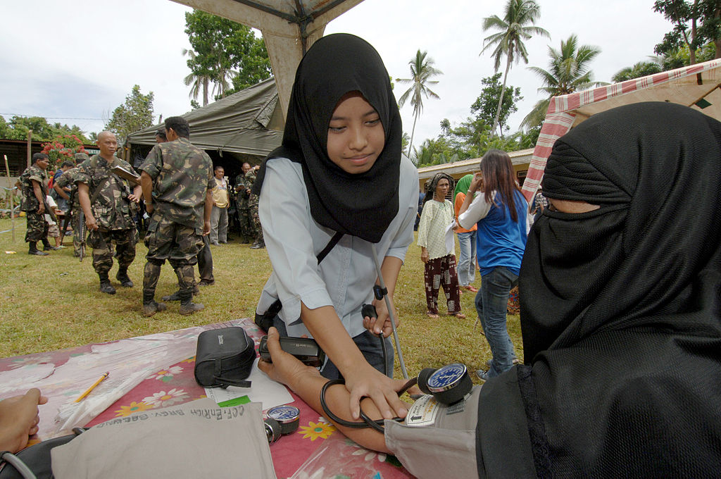 A young Muslim volunteer checks a local Filipino woman's vital signs
