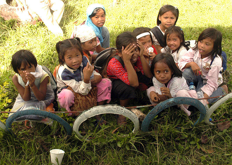 Filipino girls sit outside Paaralang Elementary School during a medical civil assistance program (MEDCAP).
