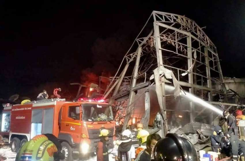 Firefighters spray foam amid twisted metal frames of a charred chemical factory in Samut Prakan