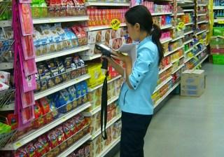 Female clerk doing inventory work in a Tesco Lotus supermarket