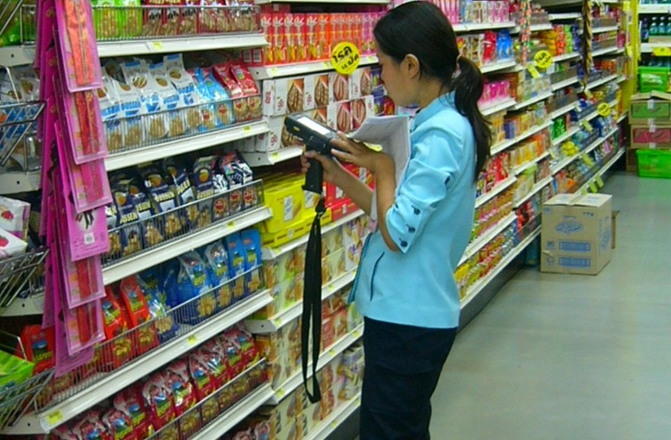 Female clerk doing inventory work in a Tesco Lotus supermarket