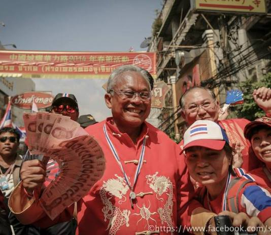 Suthep during the Bangkok Shut Down protests celebrating the Chinese New year, carrying a 100 baht notes fan