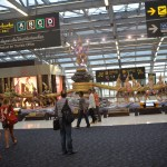 "Inside the departures terminal at Suvarnabhumi International Airport in Bangkok. Gates and VAT Refund signs and the statue of the Hindu gods known as ""stirring the ocean"""