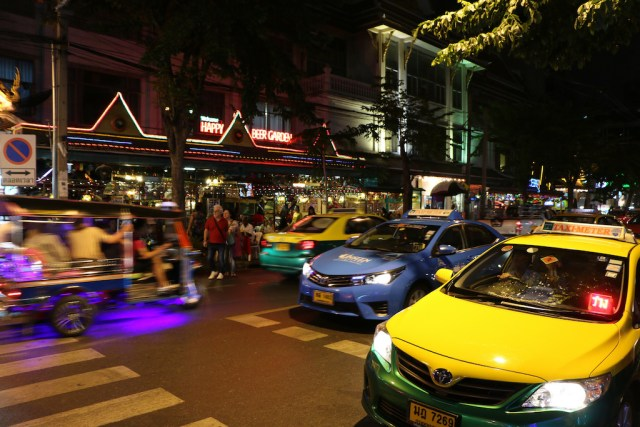 Woman straddles taxi and sidewalk, pees in Bangkok traffic