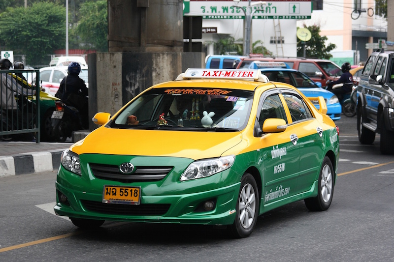 Toyota Saloon sedan taxi driving on the road in Bangkok