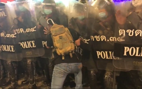 Protester pushed by riot police in Bangkok