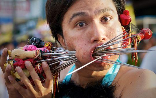 Face Piercing at Bang Neow Shrine street procession during Phuket Vegetarian Festival