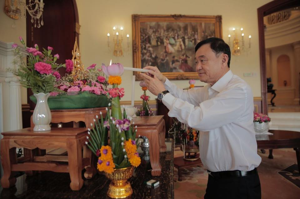 Former Thai PM Thaksin Shinawatra lighting a candle