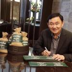 Former Thai PM Thaksin Shinawatra showing Thai rice bags