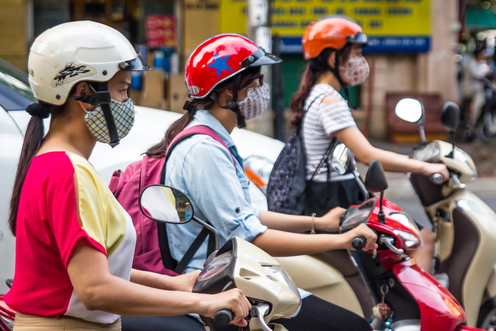 Girls wearing face masks riding scooters in Hanoi