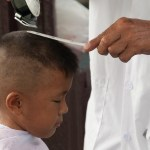 A young boy gets his hair cut in Bangkok