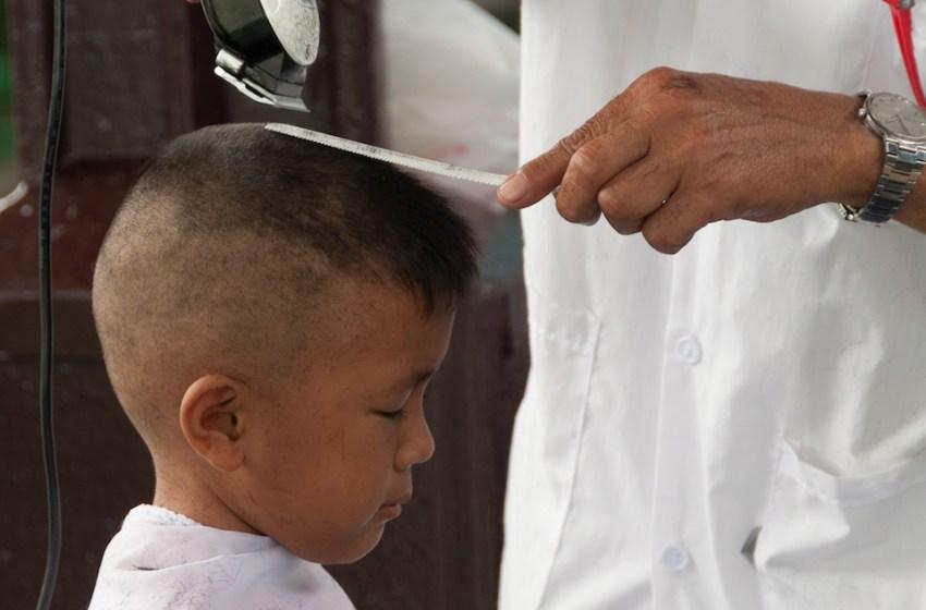 A young boy gets his hair cut in Bangkok