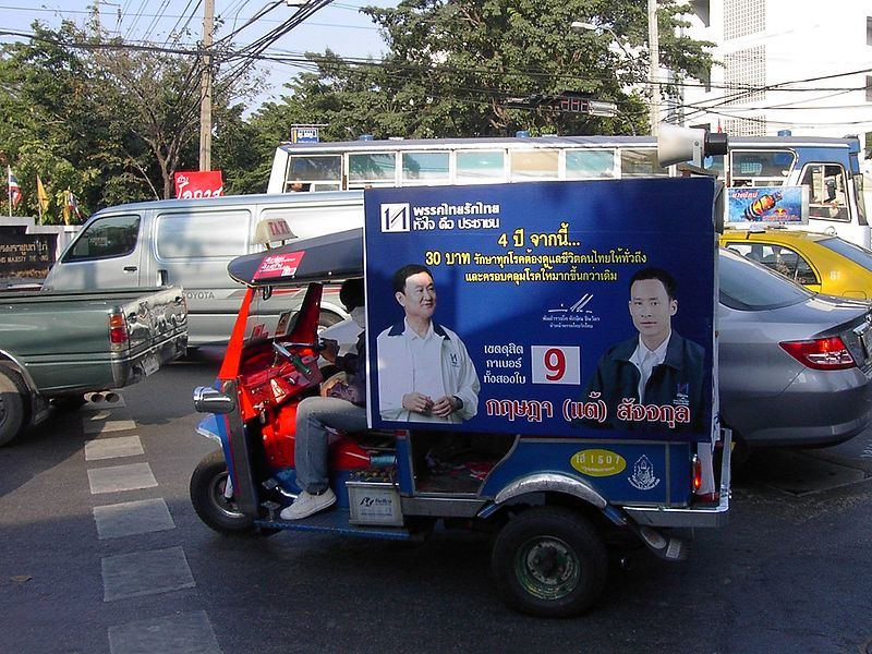 Tuk tuk carrying a poster during a Thai election campaign
