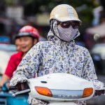Girl wearing a face mask and sunglasses wearing a Honda scooter