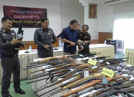 Thai police in a press conference with seized guns