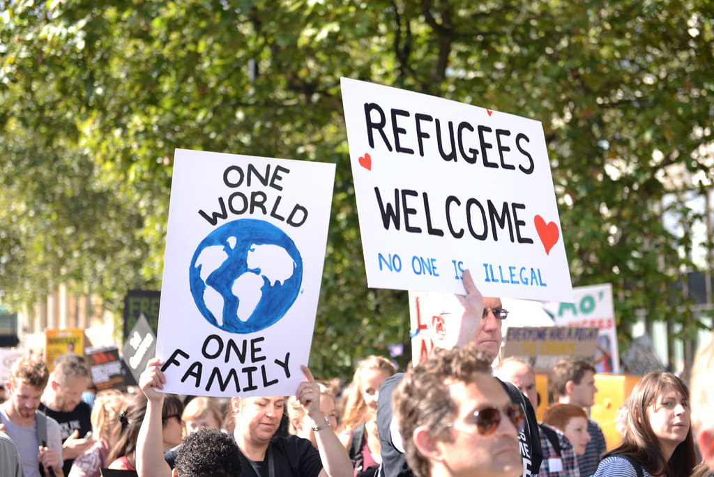 "Liberals holding banners reading ""One world - Refugees Welcome"" during a pro-immigration demonstration in Europe"