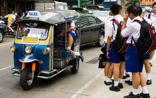 Thai students going to school by tuk tuk
