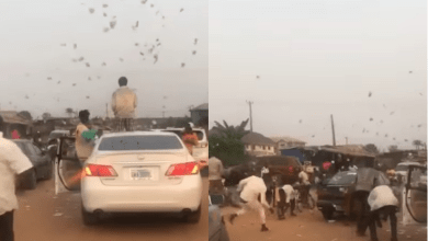 Yahoo Boys cause traffic as they stop in middle of the road to throw money in the air