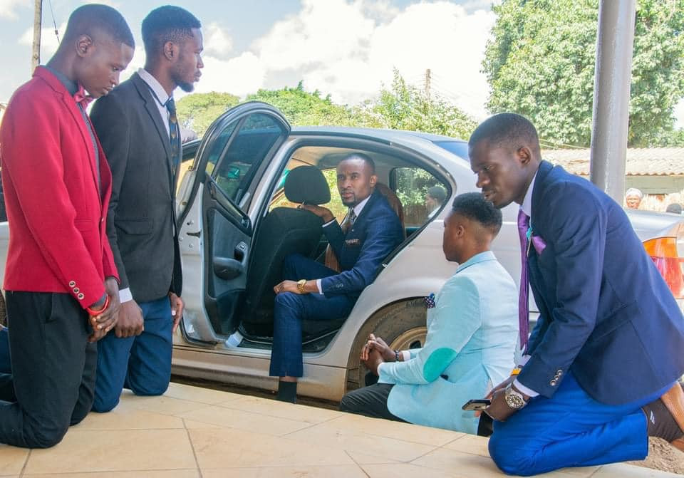 Church members kneel down to welcome their pastor