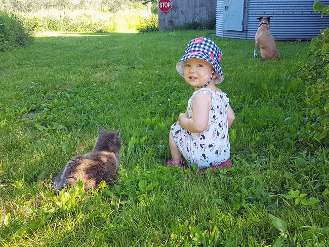 Ellie sitting in the grass with Ralph and Baxter