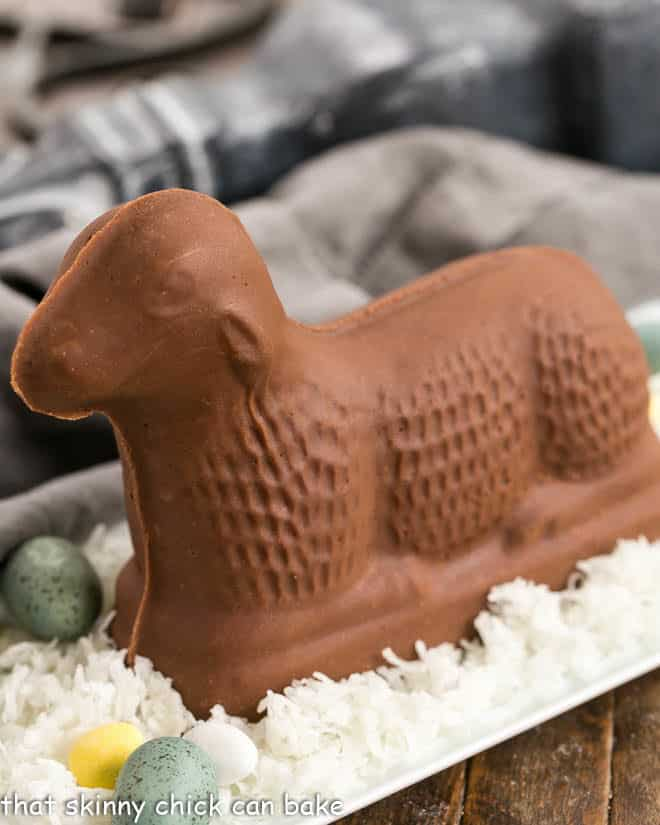 Fudge Lamb side view on a white tray of coconut on blue Easter eggs