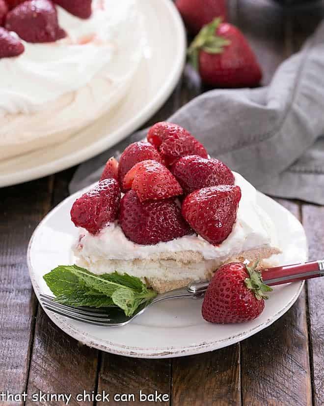 Slice of strawberry pavlova on a dessert plate garnished with fresh mint
