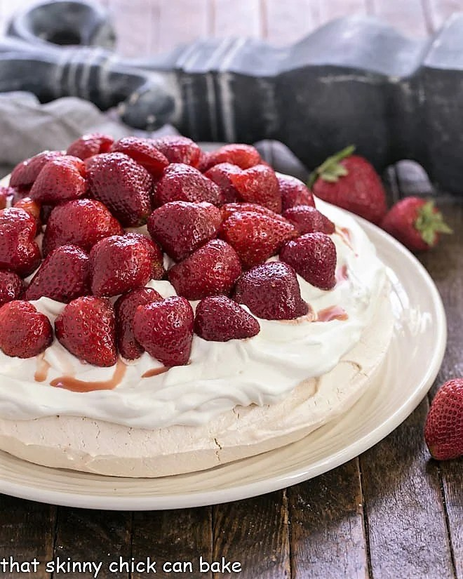 Strawberry Pavlova on a white serving plate topped with halved strawberries and whipped cream