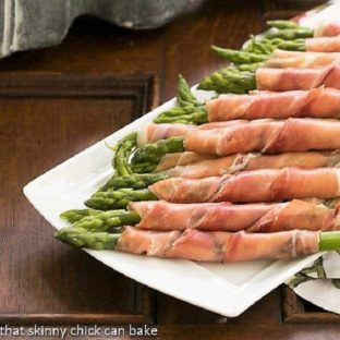 Prosciutto Wrapped Aspargus on a white tray