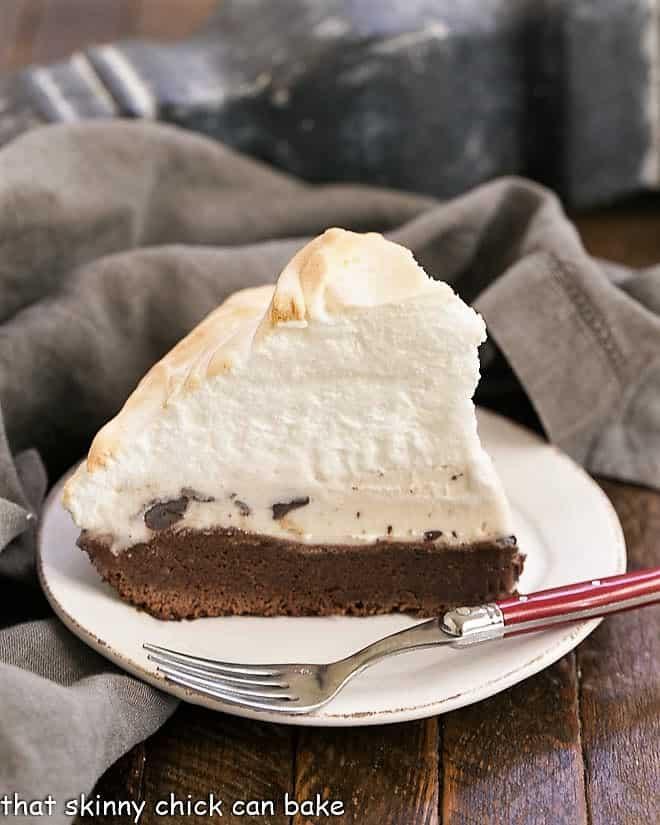 Slice of brownie baked Alaska on a white dessert plate