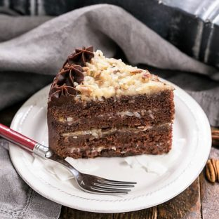 Slice of German Chocolate Cake on a dessert plate with a red fork