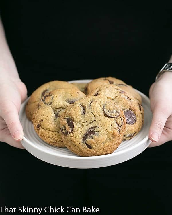 Jacques Torres' Secret Chocolate Chip Cookies on a white plate held by a girl's hands