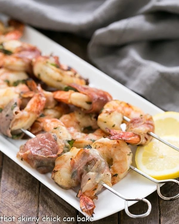 Prosciutto Wrapped Shrimp with Basil Lemon Marinade skewered and lined up on a white platter