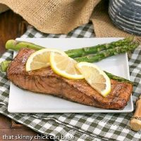 Grilled Asian Salmon garnished with lemon slices and served with asparagus on a square white plate