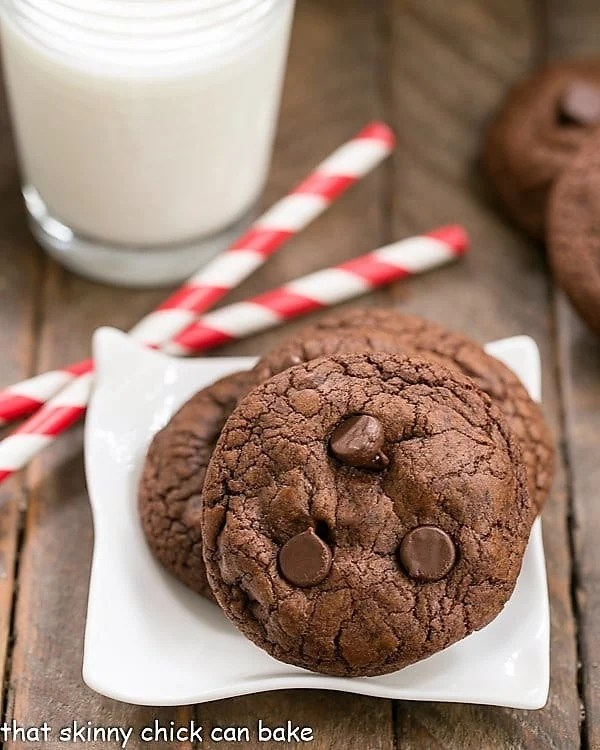 Triple Chocolate Cookies on a square white plate with red and white straws and a glass of milk