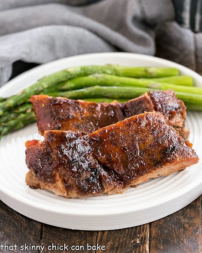 Oven Baked Ribs on a white plate with asparagus spears