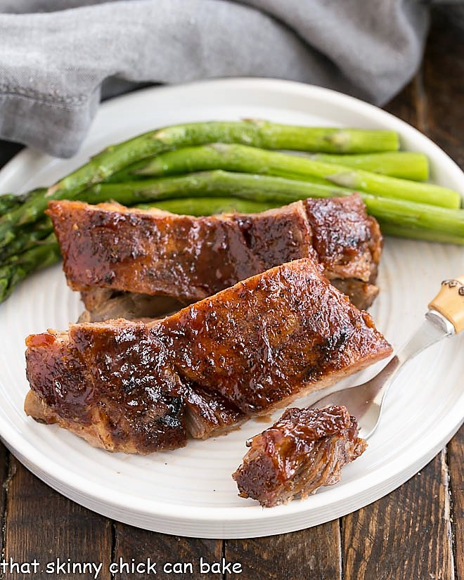 Tender bite of rib meat on a fork removed from a plate with two ribs and asparagus