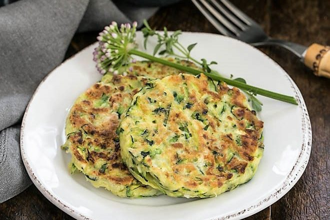 Zucchini fritters on a round white plate with herb garnish