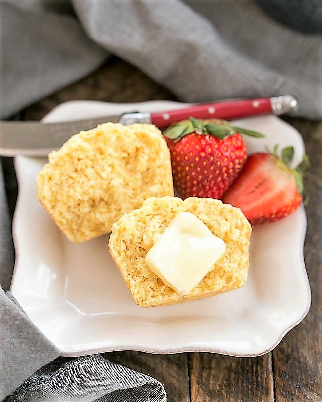 Buttermilk Corn Muffin cut in half with a pat of butter on a square white plate