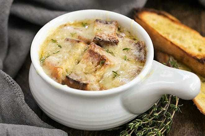 Classic French Onion Soup - A rich onion laden broth flavored with herbs, white wine and cognac and topped with cheesy toast!