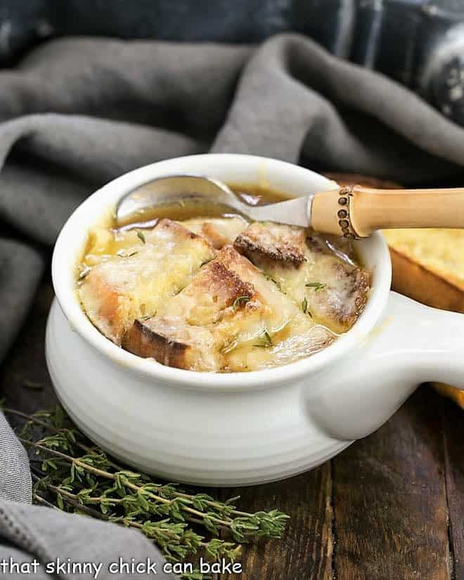 Classic French Onion Soup in a white soup bowl with a bamboo handled spoon