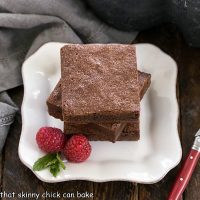 3 fudgy brownies stacked on a square white plate with 2 raspberries and a sprig of mint