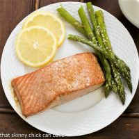Overhead view of Grilled Cedar Plank Salmon on a white plate with asparagus and lemon slices