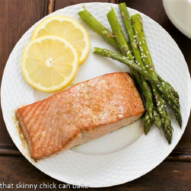 Overhead view of grilled salmon on a white plate with asparagus and lemon slices