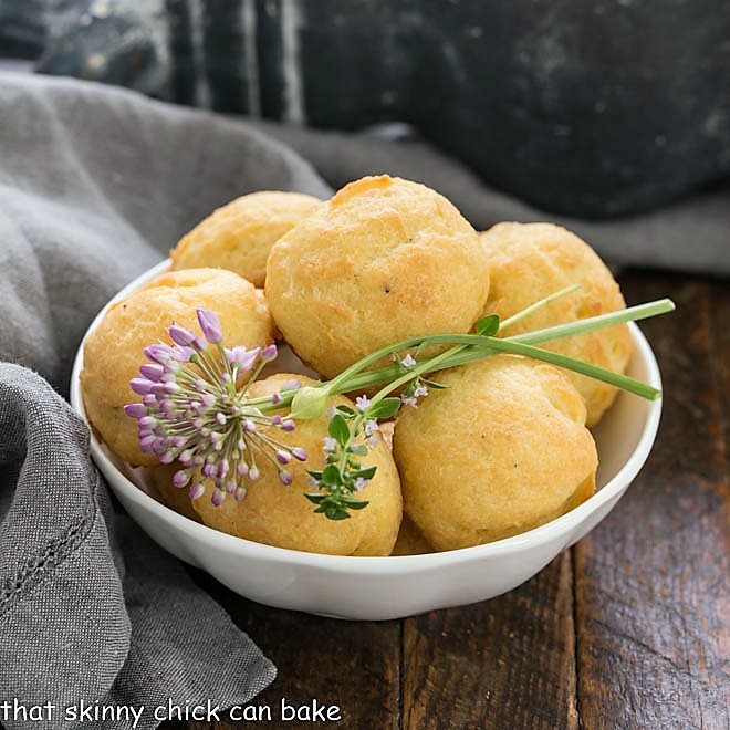 Bowl of cheese puff with chive and thyme garnishes