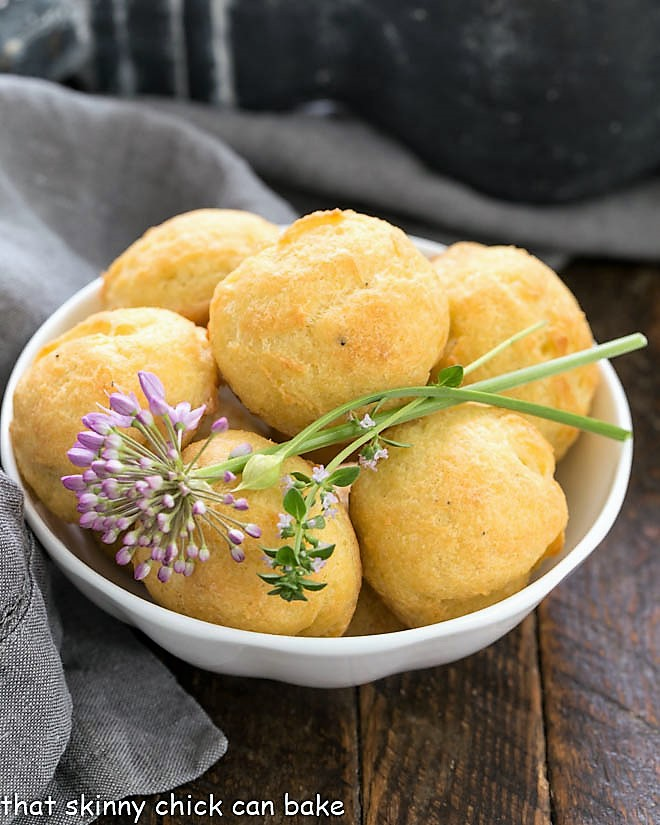 Gougères in a white bowl with herb garnishes
