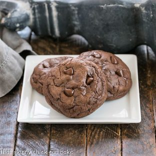 3 chocolate cookies on a square white ceramic plate