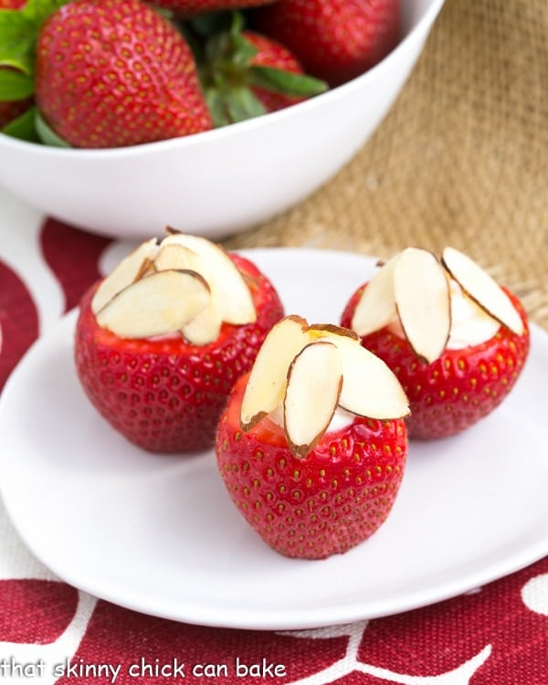 Cheesecake Stuffed Strawberries on a small oval plate topped with sliced almonds